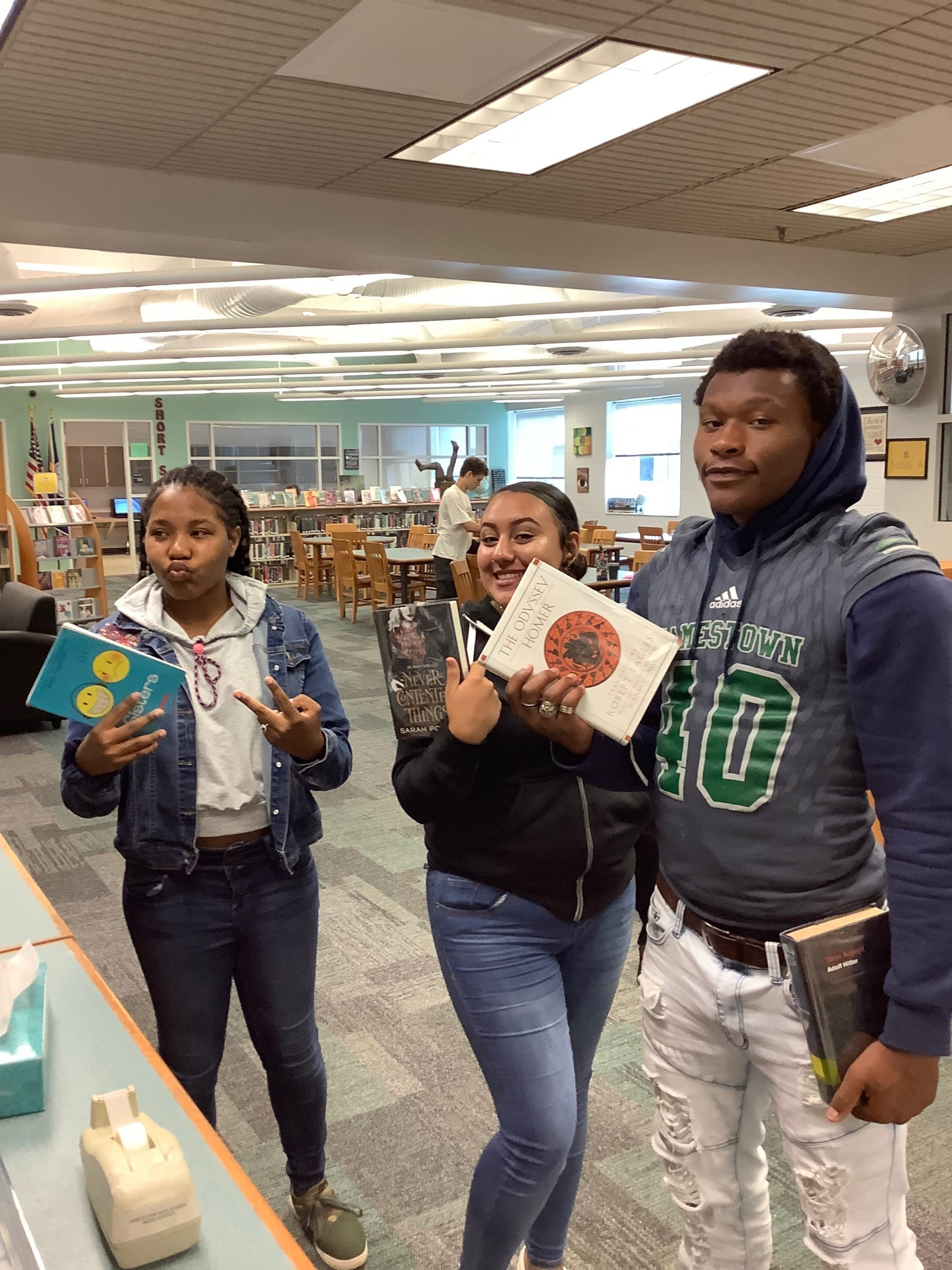 three students standing in the library showing their books and posing