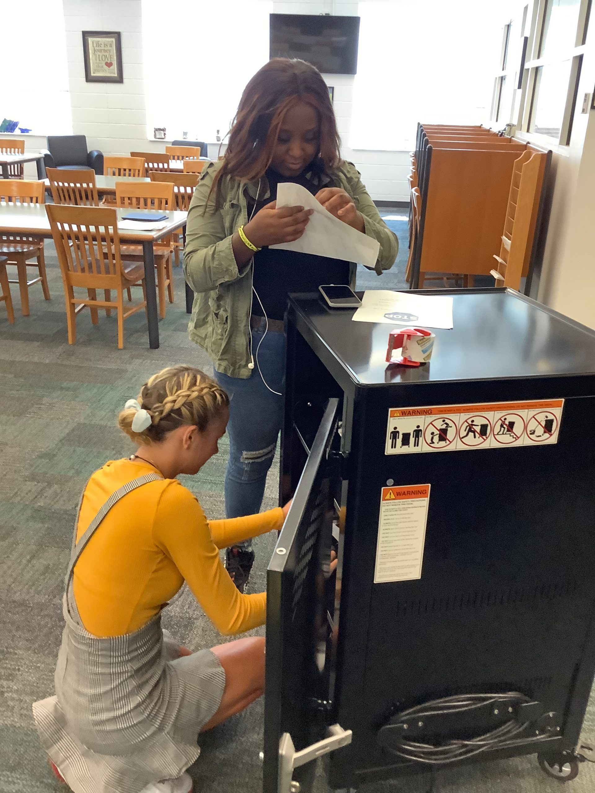 two female students putting stickers on laptops in a laptop cart in the library