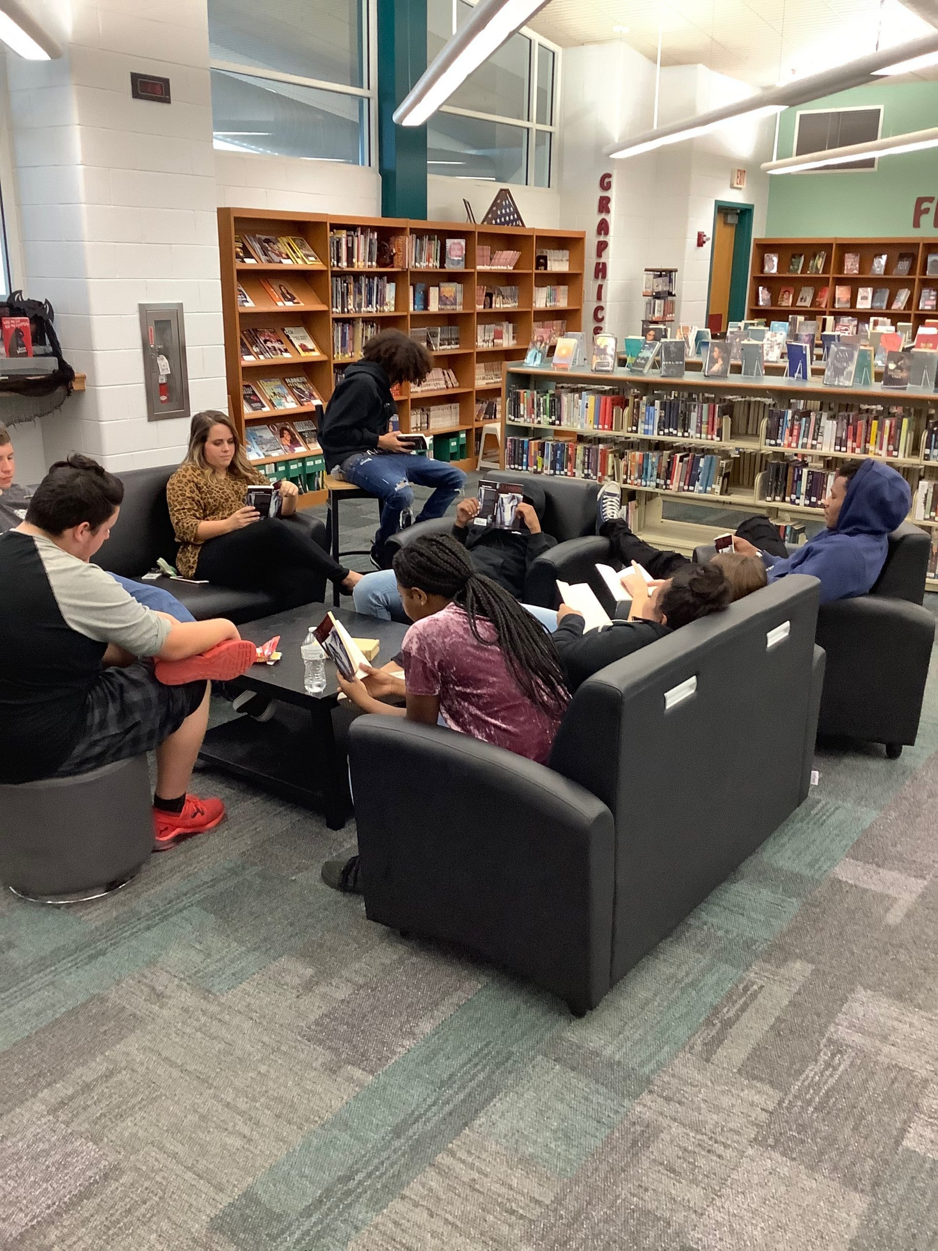 a group of students sitting on couches and chairs in the library reading books