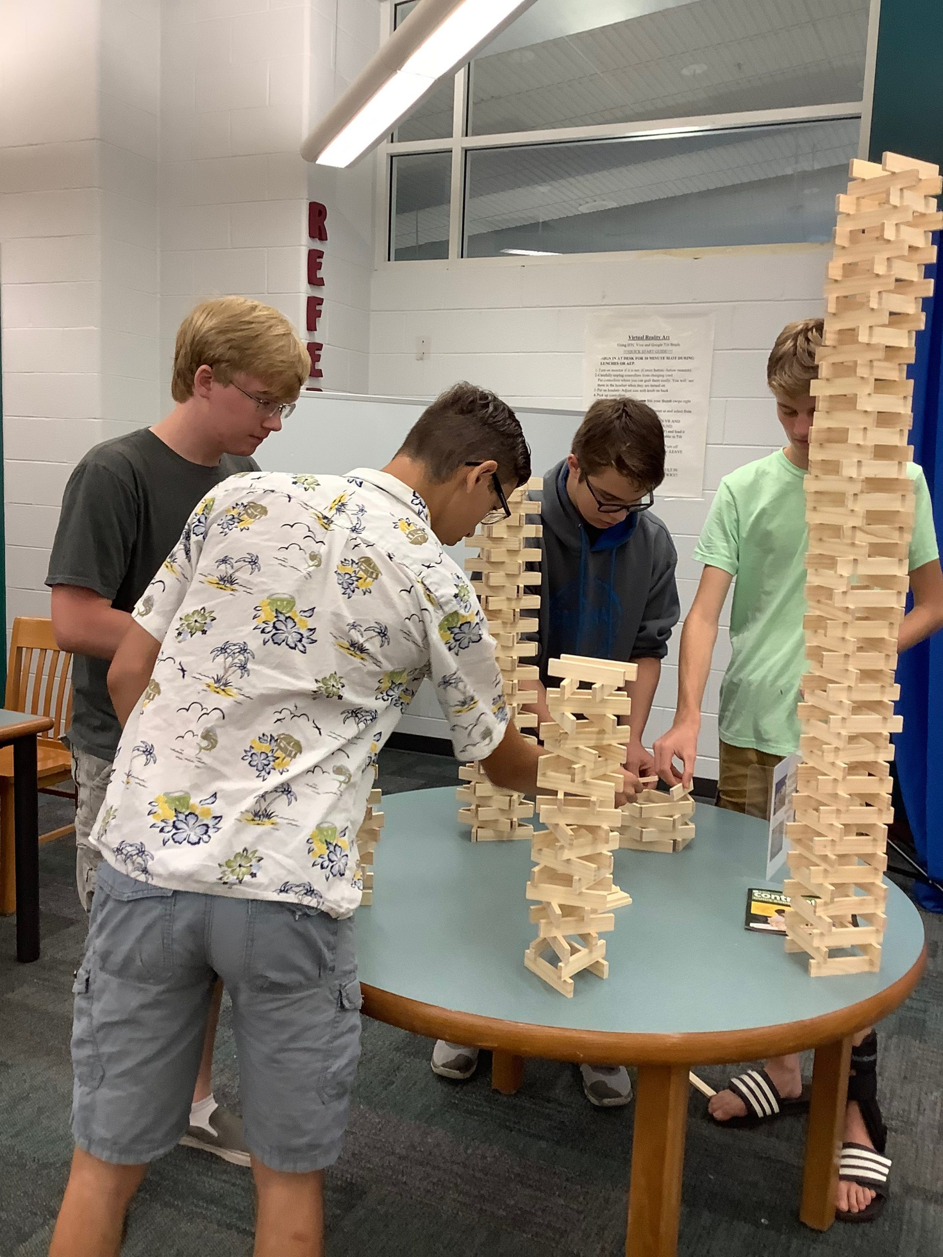 four male students standing around a table with several wooden plank structures one very tall