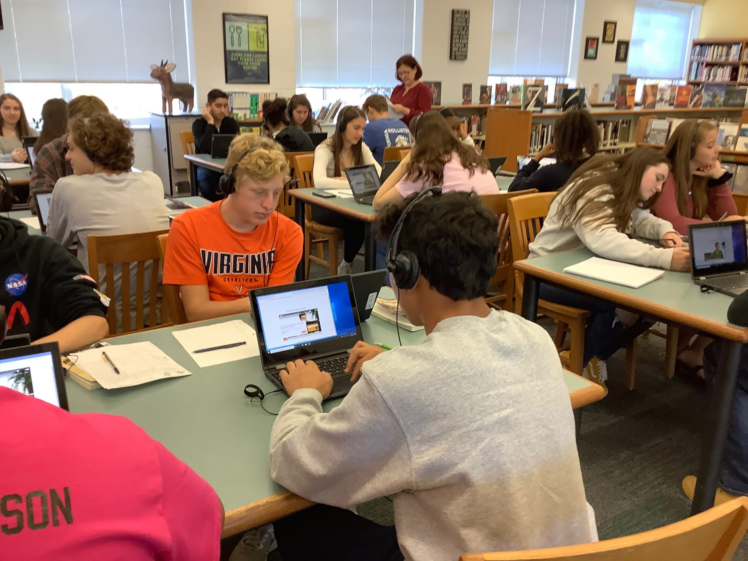students seated in a library looking at laptops with headphones on