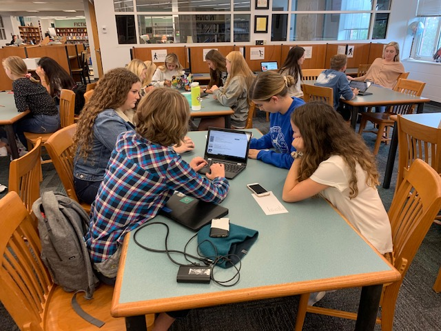 room full of students seated a tables in the library using laptops