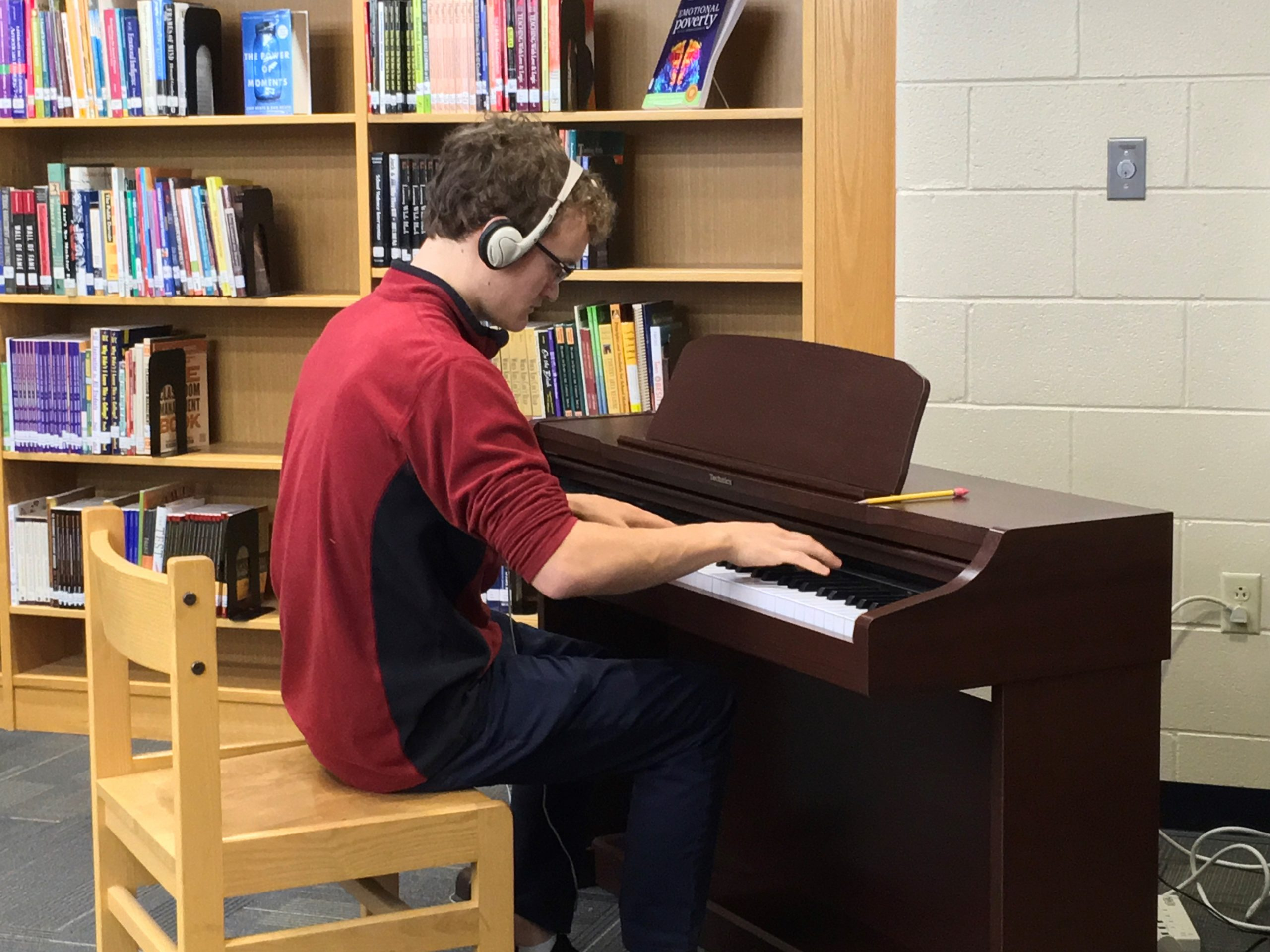 A student plays piano in the library.