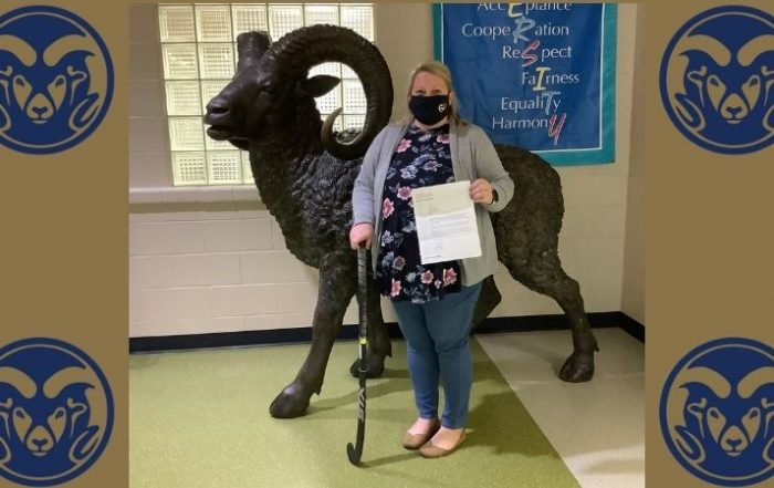 Mrs. Engtrom poses with grant letter in front of Ram Statue.