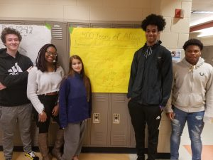 Students from Ms. Norton's history class pose with student created posters on the amendments effecting the African slaves of the United States.