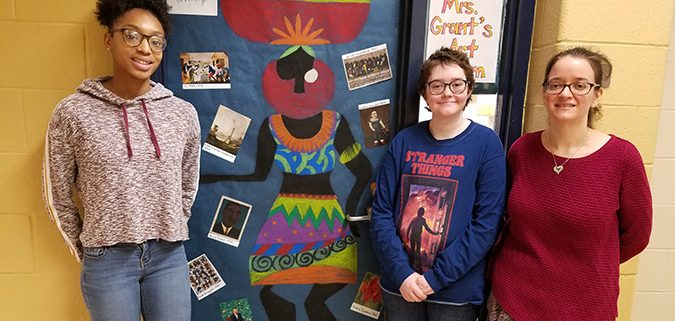 Mrs. Grant and 2 students stand by their Black History Month Door Decoration.