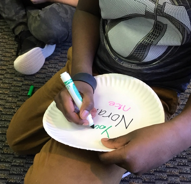 child writing on paper plate