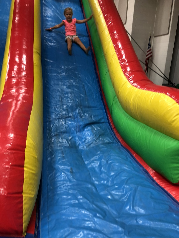 child goes down inflatable slide