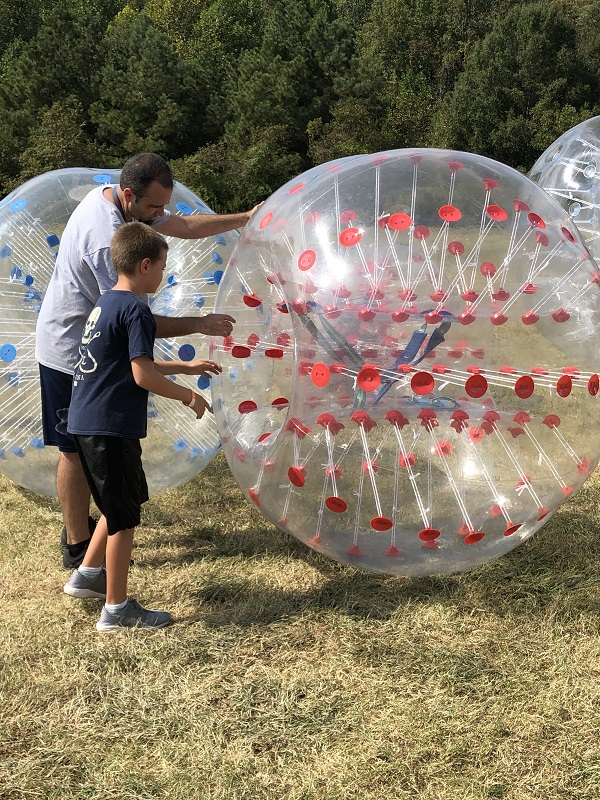 Child climbs into blow up ball