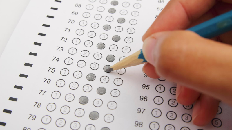 Student filling out Scantron sheet
