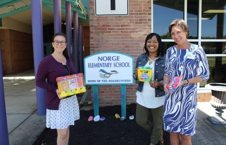 Sentara employees with Norge Elementary principal holding school supplies
