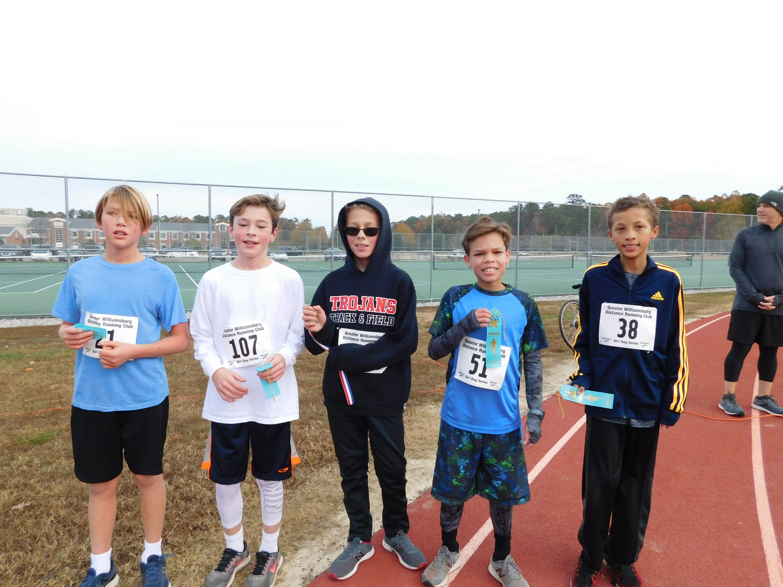 Boys after finishing their 1.5 mile event showing their ribbons