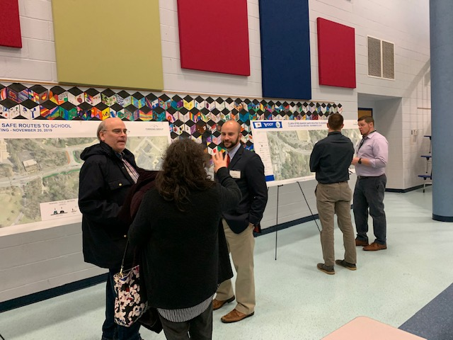 Community members, Timmons Group engineers and James City County planner stand in front of transportation project models