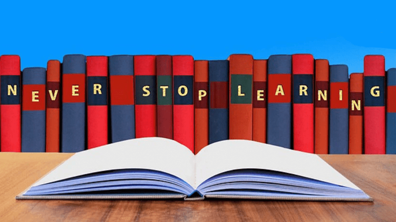 "Clipart of a book open with text saying ""Never Stop Learning"""