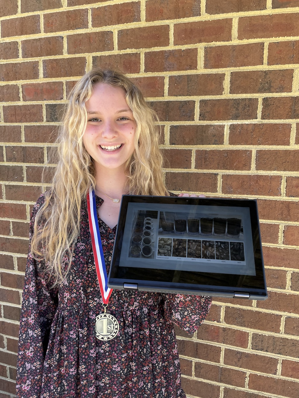 Jamestown student wearing medal and showing science project on tablet